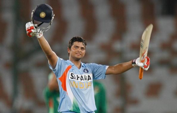India cricketer Suresh Raina (R) raises